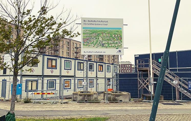 Byggskylt med en bild på Bulltofta och blå text står framför en byggarbetsplats