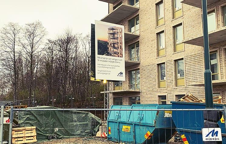En stor vit byggskylt med blå text för Midroc står framför en byggarbetsplats